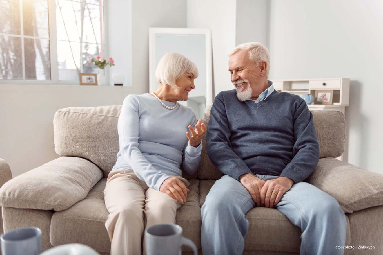 Foto eines fröhlichen älteren Paares auf dem Sofa
